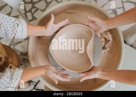 Two sets of hands giving heart shape to a clay bowl. top view - Stock Photo