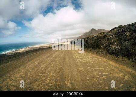 Off road ground view straight way and wild sand beach at the en in background - concept of adventure and alternative nature around lifestyle - tourism