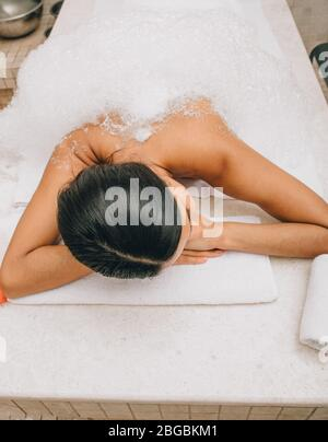 Soap massage of a beautiful woman in a hammam, top view. Procedures in the Turkish bath improves the skin and stops the aging process - Stock Photo
