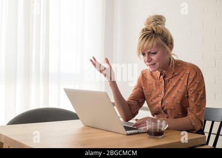 Young woman disappointed while working on laptop. He is sitting at table at home.