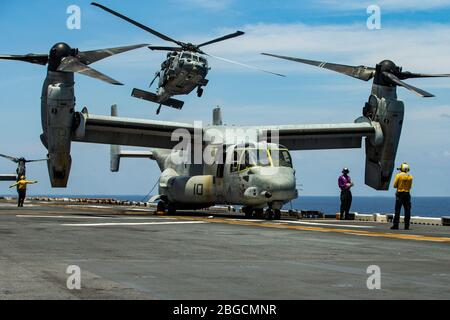 """SOUTH CHINA SEA (April 18, 2020) An MH-60S Sea Hawk helicopter assigned to the """"Island Knights"""" of Helicopter Sea Combat Squadron (HSC) 25, aboard amphibious assault ship USS America (LHA 6), takes off from the flight deck of the America. Marines and Sailors aboard the America regularly conduct flight operations while underway to maintain their readiness to respond to contingencies. America, flagship of the America Expeditionary Strike Group, 31st MEU team, is operating in the U.S. 7th Fleet area of operations to enhance interoperability with allies and partners and serve as a ready response f - Stock Photo"""