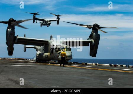 SOUTH CHINA SEA (April 18, 2020) ) An MV-22B Osprey tiltrotor aircraft with Marine Medium Tiltrotor Squadron (VMM) 265 (Reinforced), 31st Marine Expeditionary Unit (MEU), takes off from the flight deck of amphibious assault ship USS America (LHA 6). Marines and Sailors aboard the America regularly conduct flight operations while underway to maintain their readiness to respond to contingencies. The Osprey is a long-range troop transport aircraft that can be deployed at a moment's notice, enabling the Blue-Green team to rapidly respond to crises. America, flagship of the America Expeditionary St - Stock Photo