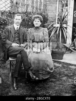 Two people, a man and a woman, sit posing for a portrait in the garden. England, circa 1890
