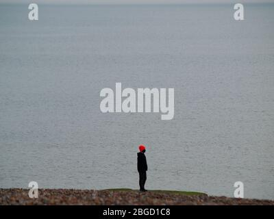 A solitary figure looks out to sea in Brighton