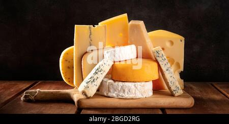 Cheese panorama, many different types of cheeses, a side view on a dark background - Stock Photo