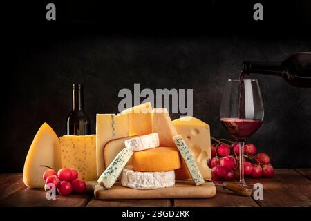 Cheeses with grapes and pouring wine, a side view on a dark background with copy space - Stock Photo