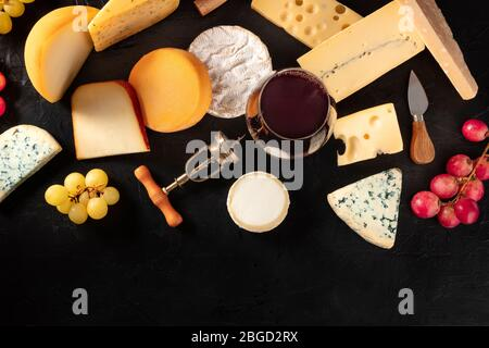 Cheese and wine, overhead flat lay on a dark background with a place for text - Stock Photo
