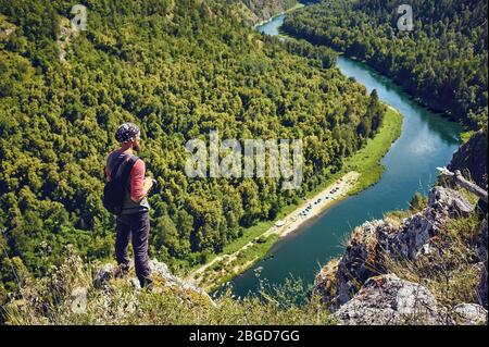 A tourist with a backpack and a camera on a rock enjoying a view of the river valley - Stock Photo