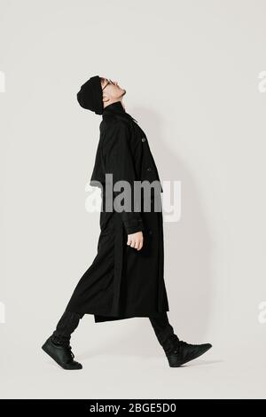 Full length side portrait of walking Millenial young man wearing black clothes, hat on white background Stock Photo