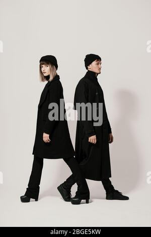 Full length side portrait of a Millenial young man and woman walking in different directions, wearing black clothes, hats on white background with cop - Stock Photo