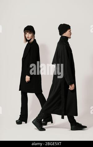 Full length side portrait of a Millenial young man and woman walking in different directions, wearing black clothes, hats on white background with cop Stock Photo