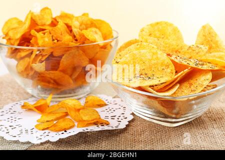 Homemade potato chips in glass bowls on table - Stock Photo