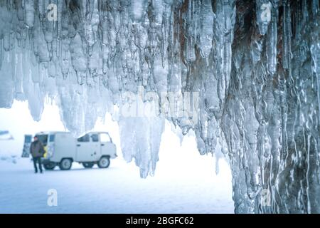 Travelling in winter, a man standing on Frozen lake Baikal with Ice cave in Irkutsk Siberia, Russia - Stock Photo