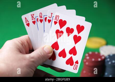 Holding the winning hand royal flush hearts selective focus - Stock Photo
