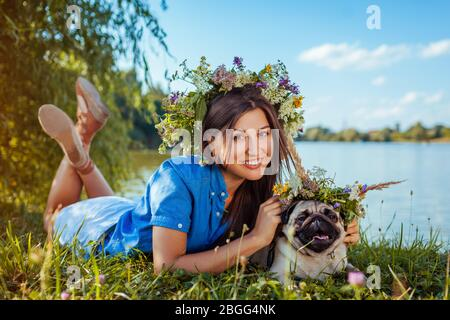 Pug dog and master lying by lake wearing flower wreaths. Happy puppy and smiling woman enjoying spring nature outdoors - Stock Photo