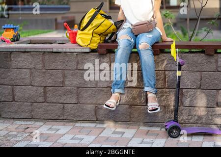Young adult woman wearing casual clothes sitting on wooden bench at children playground and looking after playing kids on warm sunny day outdoors - Stock Photo