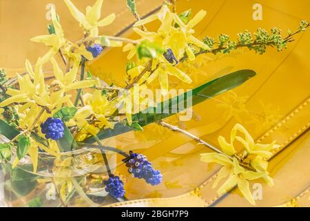 Blurred floral background, double exposure, yellow handbag and bouquet of colorful flowers, top view, selective focus. Concept of spring or summer