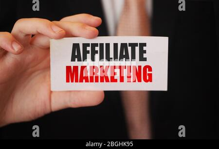 Affiliate Marketing words in card in businesman hand. Refer a friend business model concept - Stock Photo