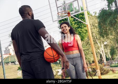 Outdoors Activity. African couple standing on basketball court man back view with ball looking at woman walking towards laughing playful - Stock Photo