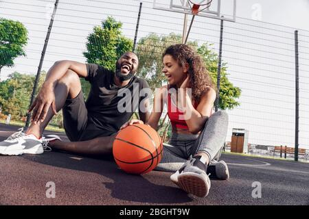 Outdoors Activity. African couple sitting with ball on basketball court laughing joyful - Stock Photo