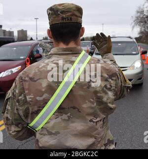 New York Army National Guard Sgt. Joseph Ryan of Holbrook, N.Y., assigned to the 1st Battalion, 69th Infantry Regiment, waves a motorists forward at the entrance of a drive-thru COVID-19 sampling site in the Bronx, N.Y., April 3, 2020. New York National Guard members are supporting the multi-agency response to COVID-19. (U.S. Air National Guard photo by Senior Airman Sean Madden) - Stock Photo