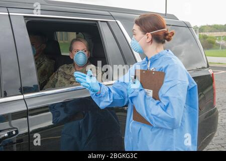 Texas Army National Guard Spc. Amanda Patton, assigned to the Medical Readiness Clinic Detachment, performs a mock drive-through COVID-19 screening with Major General Tracy R. Norris, the Adjutant General of Texas on March 18, 2020. Drive-through COVID-19 screening centers allow the public to receive COVID-19 tests while limiting physical contact to better protect healthcare workers and others waiting to be tested. (U.S. Army National Guard Photo by Andrew Ryan Smith/Released) - Stock Photo