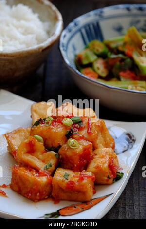 Top view simple non meat diet for lunch in daily family meal, tray of vegan dish, tofu cook with tomato sauce, fried okra, rice for healthy lifestyle - Stock Photo