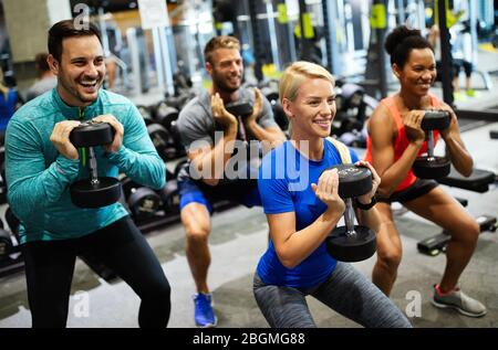 Group of friends smiling and enjoy sport in gym - Stock Photo