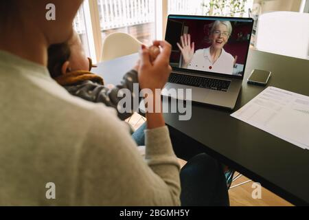 Woman with her daughter having video call with her mother. Woman connecting with her mother on a video call while at home. - Stock Photo