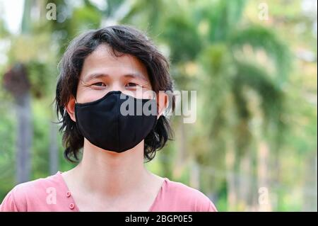 Man wearing a cloth mask in park public area protect himself from risk of disease, people prevent infection from coronavirus Covid-19 or Air pollution - Stock Photo