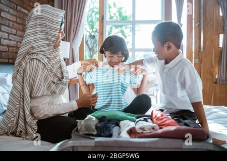 Mother and her child prepare clothes and put in suitcase for carried when mudik go to back village home