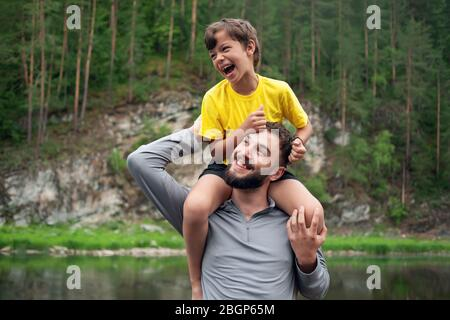 Father and son are smiling while spending time together. Little boy sits on father neck - Stock Photo