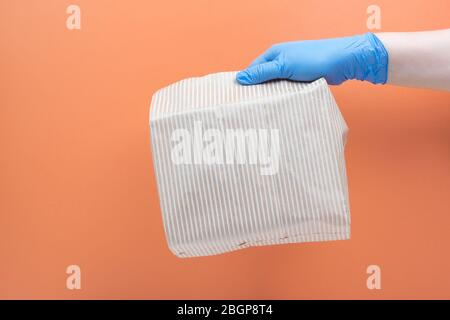 A bag of food in a gloved hand. Food delivery, safe food takeout. Takeaway food. - Stock Photo