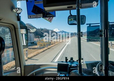 The peak of Mount Fuji San with white snow cap will be seen from the bus windshield when arrive Kawaguchiko city, Japan February 9,2020 - Stock Photo