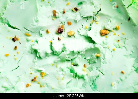 Close-up view of natural food background from homemade freshly cooked cold pistachio pastel green colored ice-cream dessert with ground-up nuts. Top v