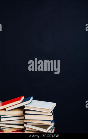 many stacks of educational books in the university library on a black background - Stock Photo