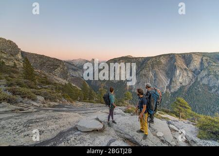 Three hikers looking at Half Dome from El Capitan sunset Yosemite - Stock Photo