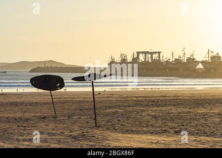 Sunset on the Beach in Essaouira Morocco with a view of the Harbor and Umbrellas - Stock Photo