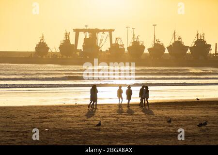 Sunset on the Beach in Essaouira Morocco with Silhouettes of People and Docked Boats - Stock Photo