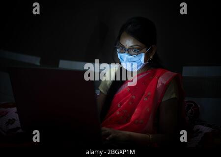 Young indian Woman wearing mask working on her laptop late night, freelancer working from home. Coronavirus,Covid-19. stay home stay safe, woman in qu