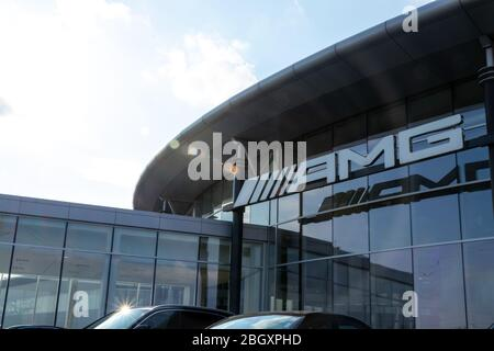 Mercedes-AMG logo hanging at the front of a Mercedes-Benz dealership on a sunny day.