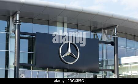 Mercedes-Benz star emblem posted on the outside of a dealership. - Stock Photo