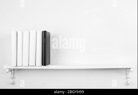 Blank books with black one on bookshelf on white wall background - Stock Photo