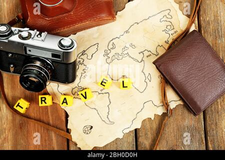 Retro camera on world map with word Travel on wooden table background