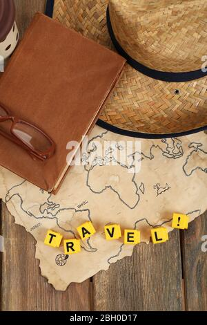 Straw hat, book and glasses with word Travel on world map and wooden planks background