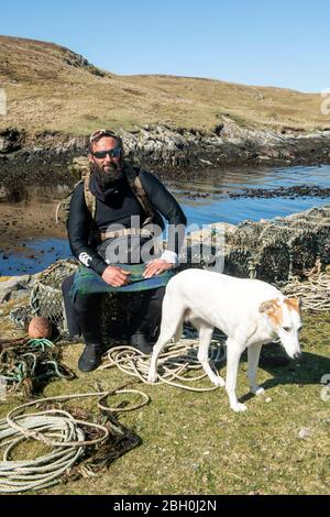 Hildasay, Shetland, Scotland, UK , 22nd April 2020, Ex-Paratrooper and charity walker Chris Lewis and his companion Jet on the island of Hildasay on the west coast of Shetland were they are self isolating during the COVID-19 pandemic. Chris is on a charity walk around the coast of the UK which he started in 2017. All money raised goes towards the SSAFA armed forces charity. The island of Hildasay is an uninhabied island and Chris and Jet are the only occupants during this tme. Photo:Dave Donaldson Credit: Dave Donaldson/Alamy Live News - Stock Photo
