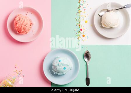 Balls of freshly cooked natural homemade colorful berries and vanilla ice cream or gelato in the ceramic plates on a pastel tricolor background, copy