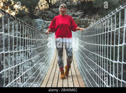 Adult woman standing on a hanging wooden bridge in the nature. Female hiker in Goynuk Kanyonu in Antalya,Turkey. - Stock Photo