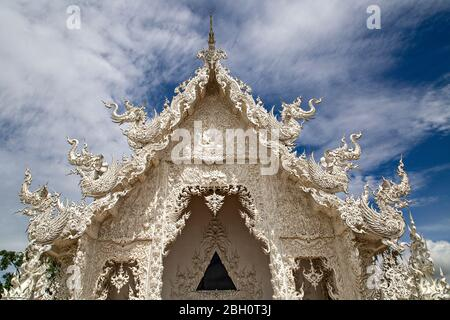 White Temple known as Wat Rong Khun with its reflection in water, in Chiang Rai, Thailand. - Stock Photo