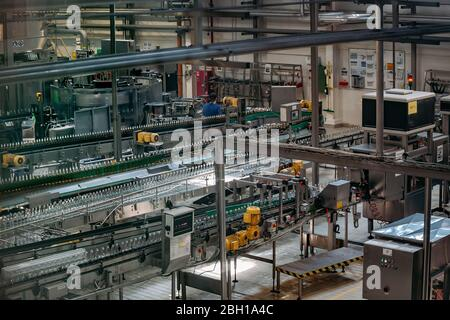 Modern automated beer bottling production line. Beer bottles moving on conveyor. - Stock Photo